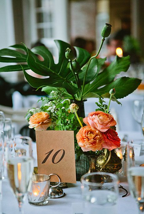 a centerpiece with tropical leaves, orange blooms and vintage metal jugs