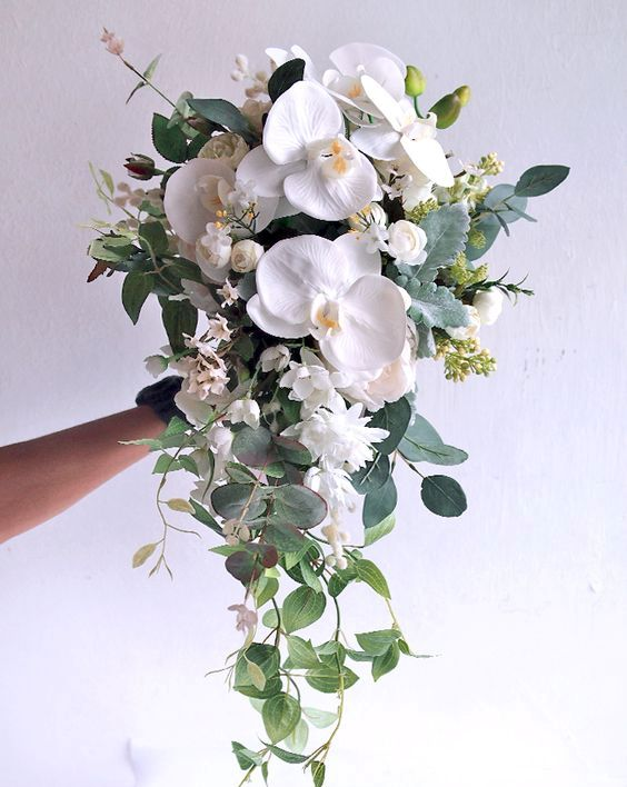 a chic textural cascading wedding bouquet with white orchids and various greenery for a chic look