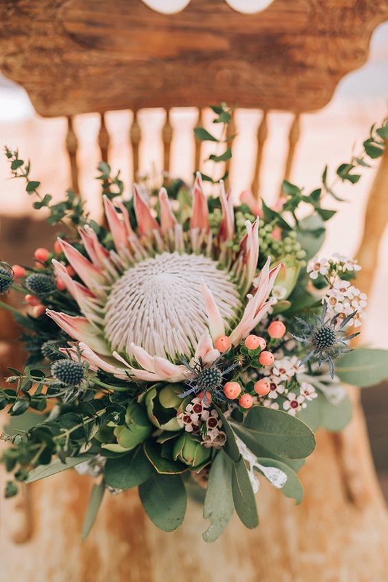 a creative and bold bouquet with a king protea, blue thistles, berries and little white blooms around