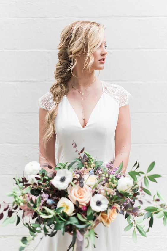 a delicate and undone twisted braid with some bangs is ideal for a modern and casual bride