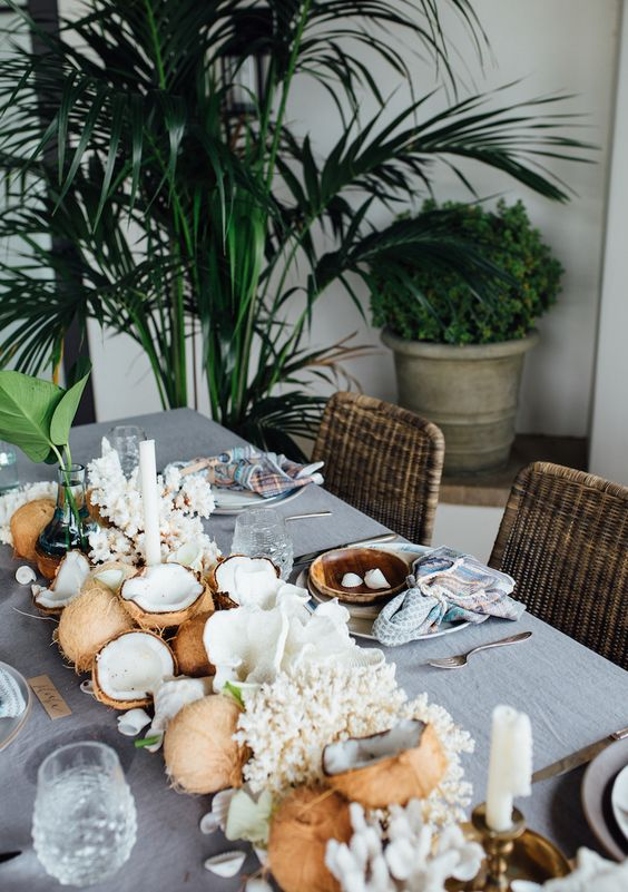 a tropical beach table runner with coconuts, corals and candles for a chic and lush look