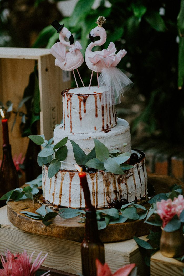 The wedding cake was a white buttercream one, with chocolate drip, greenery and plush flamingo toppers