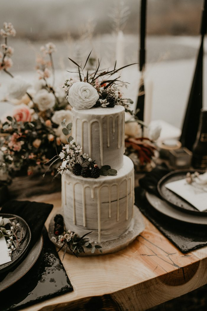 The wedding cake was grey, with creamy drip, greenery, blooms and berries