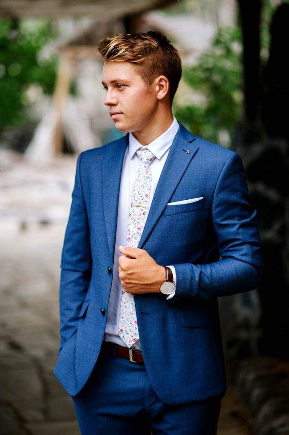a bold blue suit, a white shirt, a floral print tie for a whimsy touch