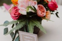 12 a bold centerpiece with pink, fuchsia and yellow blooms plus ferns for a slight tropical feel