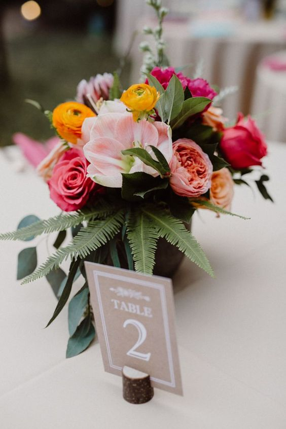 a bold centerpiece with pink, fuchsia and yellow blooms plus ferns for a slight tropical feel