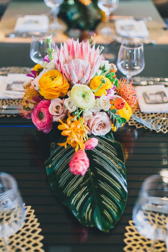 a chic tropical wedding centerpiece with a large leaf and bold blooms in pink, yellow and orange