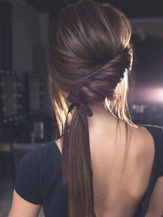 a chic twisted side low ponytail with bangs and a ribbon for an accent is ideal for a modern wedding
