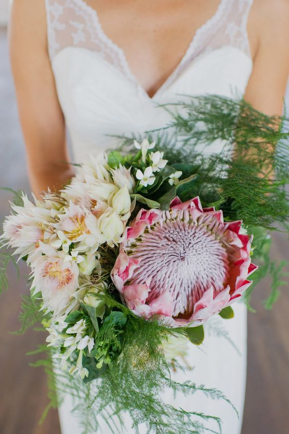 a creative and textural bouquet with a king protea, blush and ivory blooms plus ferns for a unique look