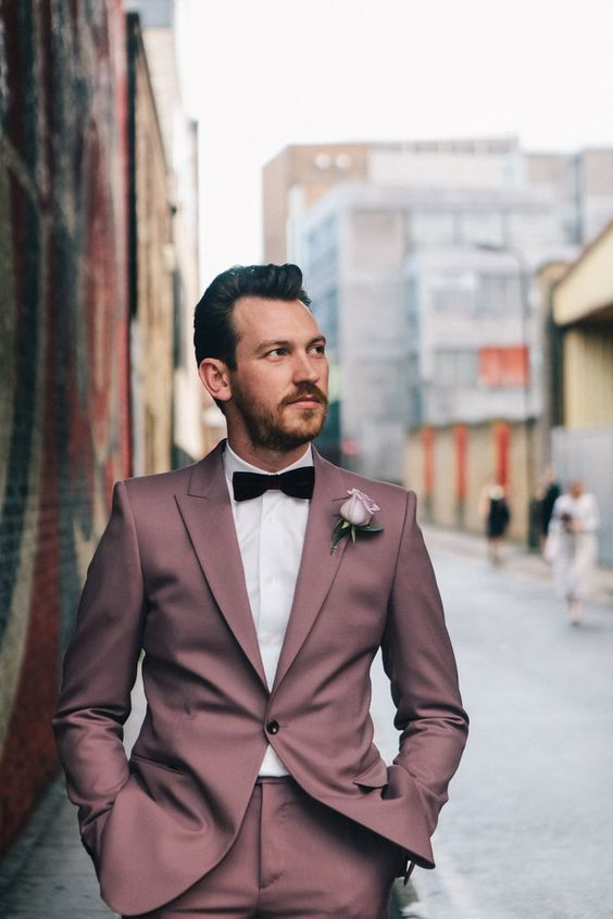 a mauve groom's suit with a white shirt and a burgundy velvet bow tie for a unique feel
