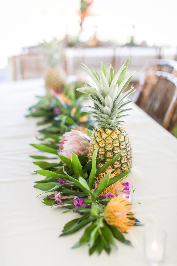 a tropical runner of greenery, king and pincushion proteas and pineapples for a cool look