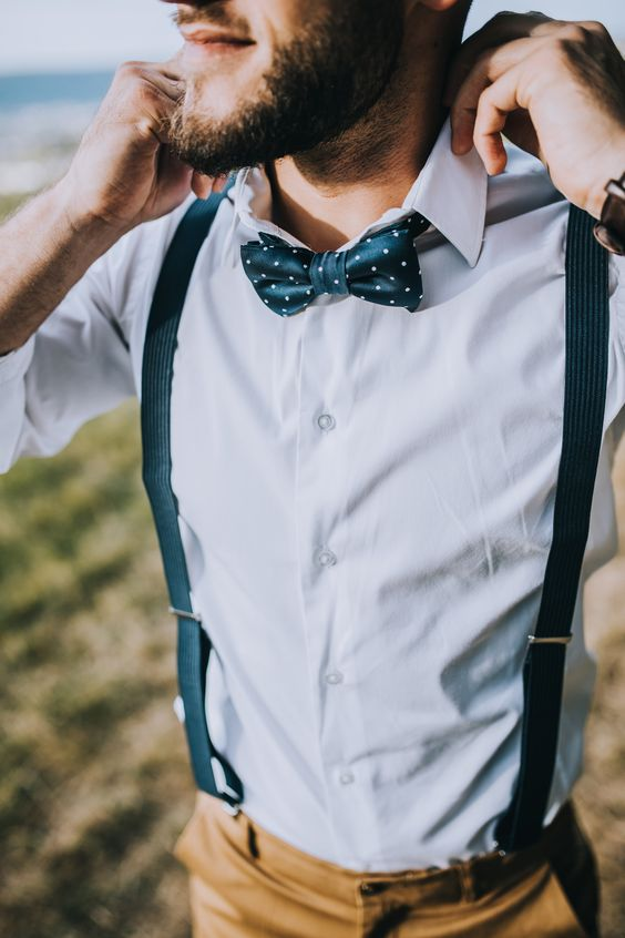 a chic look with tan pants, a crispy white shirt, black suspenders and a printed bow tie