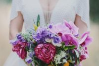 13 a colorful wedding bouquet with pink orchids, purple and fuchsia blooms and kumquats for a tropical touch
