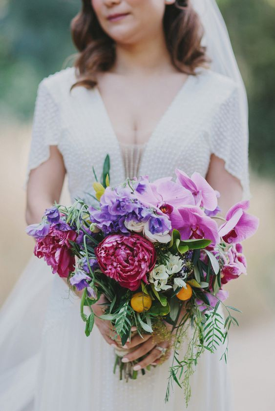 a colorful wedding bouquet with pink orchids, purple and fuchsia blooms and kumquats for a tropical touch