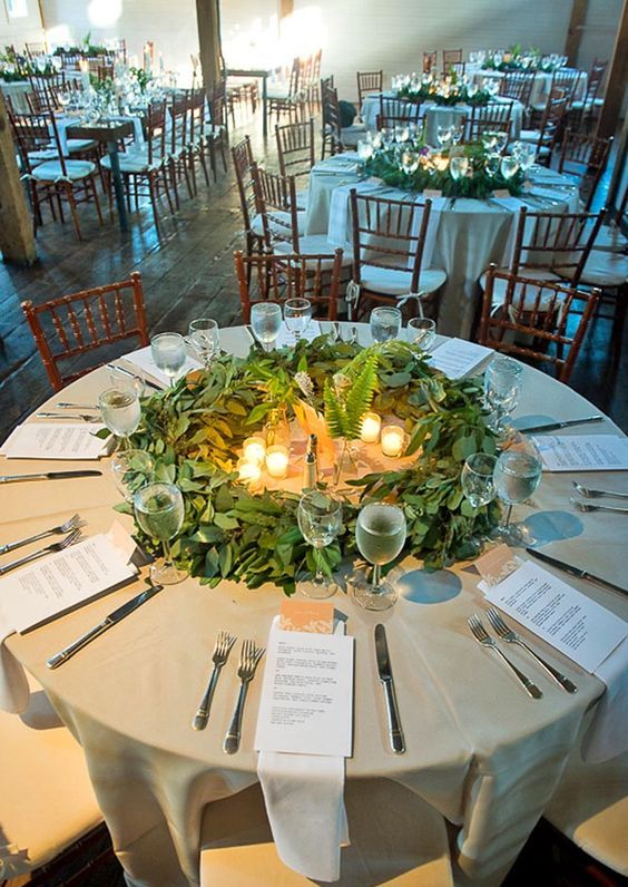 a greenery table centerpiece with eucalyptus, ferns and candles is a unique wreath like piece