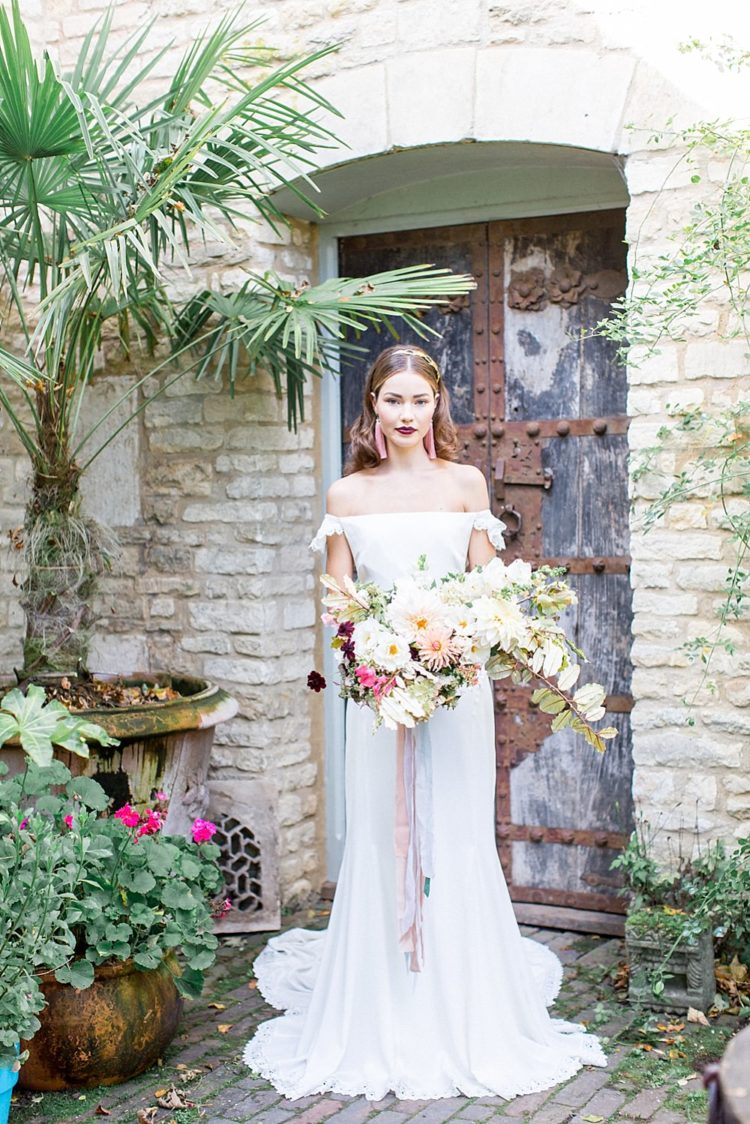 a plain fit and flare off the shoulder wedding dress with lace detailing and small train