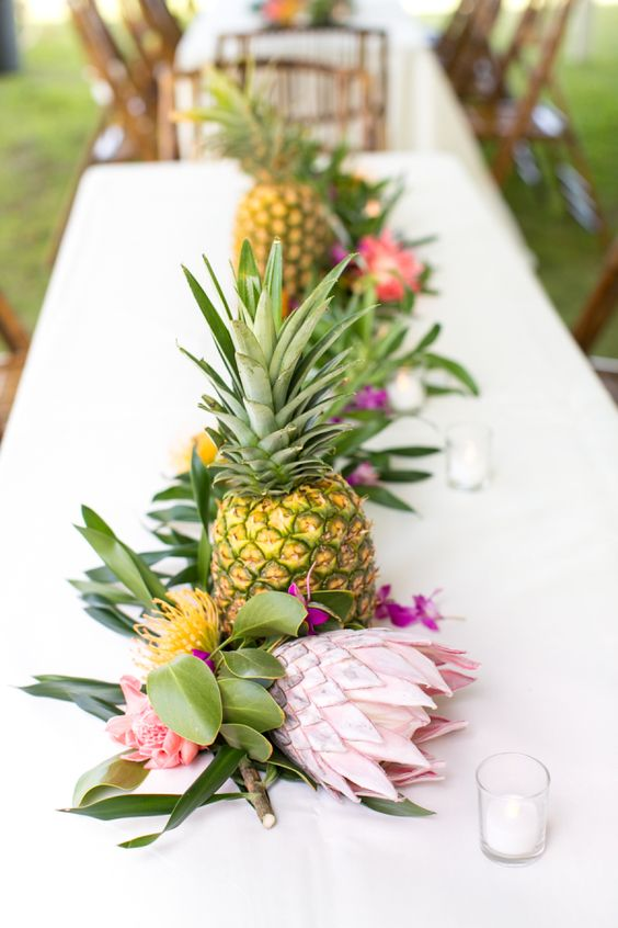 tropical greenery, king proteas, pineapples for forming a creative tropical table runner