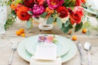 14 a bright floral centerpiece with pink peonies, parrot tulips, burgundy ranunculus and greenery