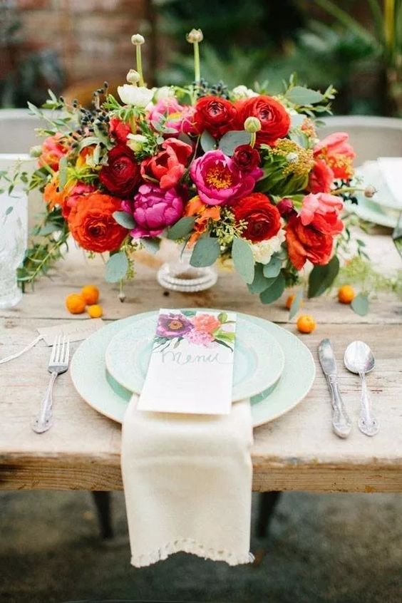 a bright floral centerpiece with pink peonies, parrot tulips, burgundy ranunculus and greenery