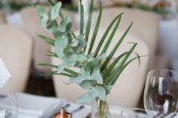 14 a cute modern centerpiece of eucalyptus and a palm leaf in a clear glass vase canbe easily DIYed