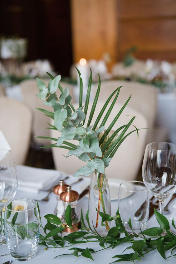 a cute modern centerpiece of eucalyptus and a palm leaf in a clear glass vase canbe easily DIYed