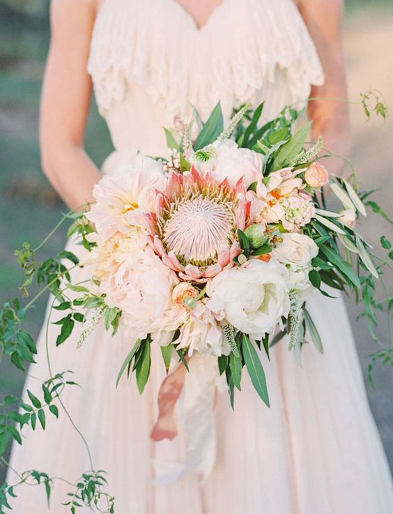 a delicate wedding bouquet with a king protea, white blooms and cascading greenry for a chic touch