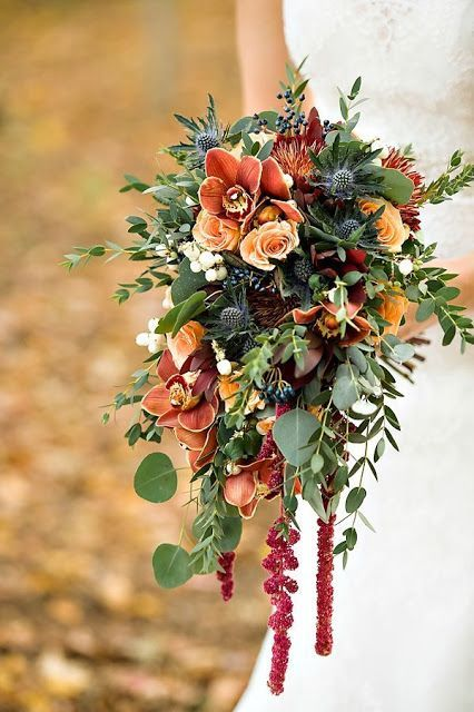 a fall boho wedding bouquet with rust colored orchids, thistles, greenery and a light cascade will make a statement