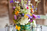 15 a bright wildflower centerpiece with touches of purple, yellow and white and herbs