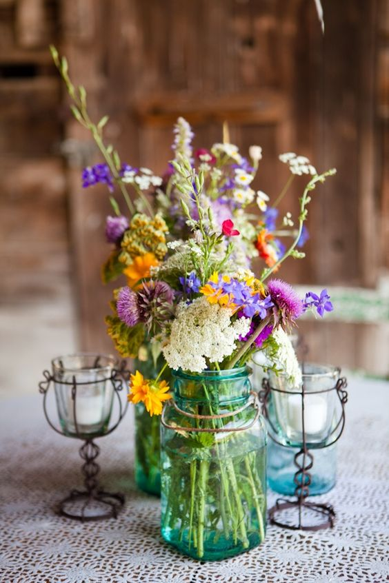 a bright wildflower centerpiece with touches of purple, yellow and white and herbs