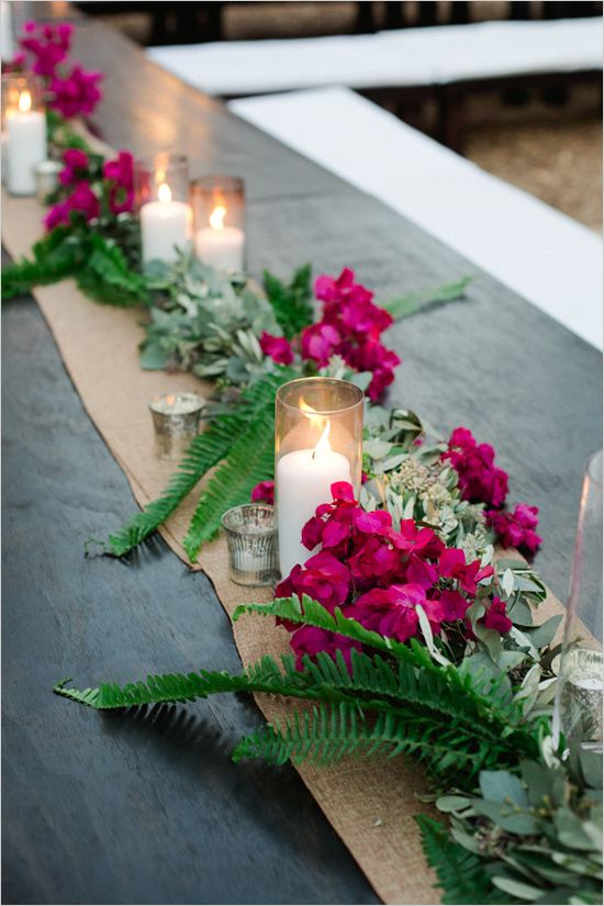 a burlap runner covered with eucalyptus, ferns, fuchsia blooms and candles for a bold touch