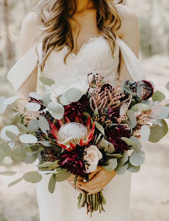 a fall boho wedding bouquet with a large king protea, burgundy dahlias, eucalyptus and herbs for a texture