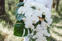 15 a fantastic cascading white orchid bouquet with monstera leaves and some more greenery for a tropical bride