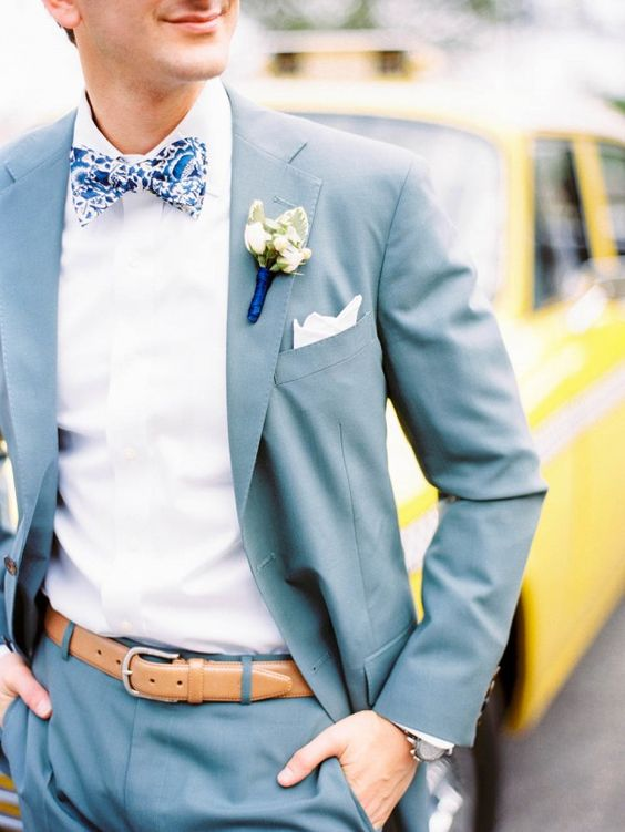 a muted blue suit, a white shirt and a blue printed floral bow tie for a summer garden wedding