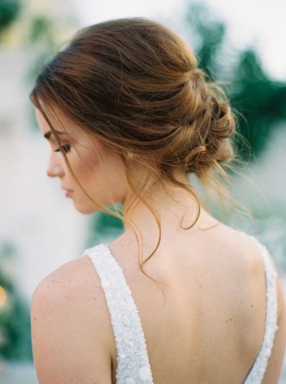 a romantic braided low updo with some bangs down for a chic and modern romantic feel