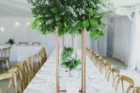 15 a tall greenery centerpiece of various types of eucalyptus and some foliage on a copper stand