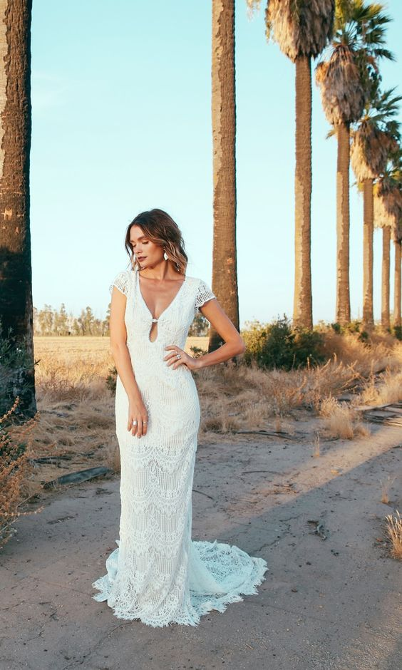 a boho lace sheath wedding dress with cap sleeves, a cutout neckline and a small train for a chic look