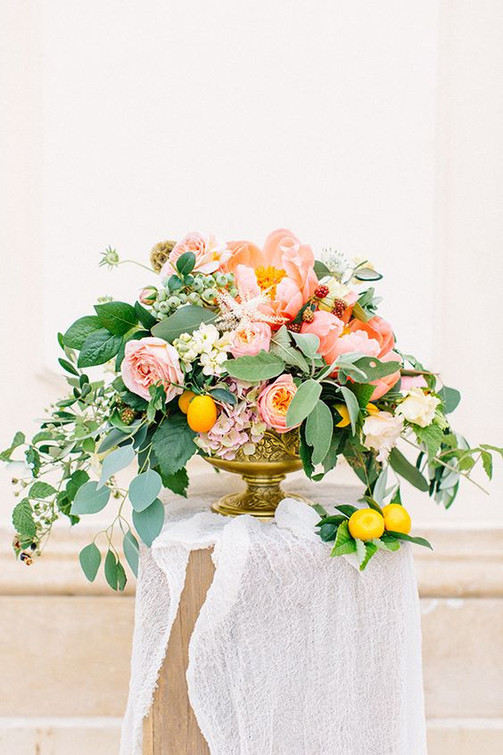 a chic and colorful peony centerpiece with pink and white blooms, cascading greenery and lemons