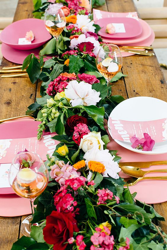 a colorful and lush tropical table runner of greenery and white, pink and burgundy blooms for a vibrant touch