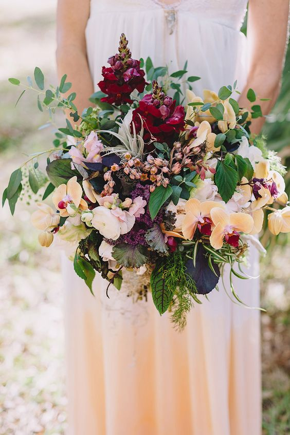 a forest wedding bouquet with yellow orchids, greenery and many textural elements for a wild look