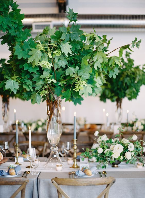a lush and oversized tall foliage centerpiece is a wow solution that makes indoors feel like outdoors