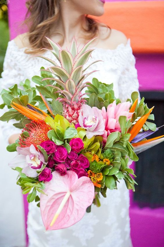 a bold bridal bouquet with hot and light pink blooms, orange touches and even a pineapple spray painted pink