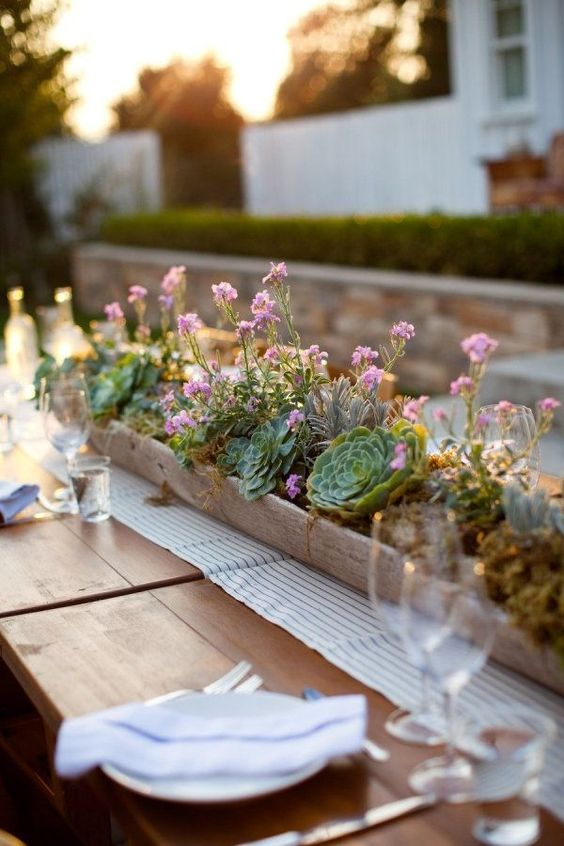 a chic casual summer centerpiece with pink blooms, moss and succulents in a wooden box