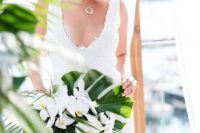 17 a glam tropical wedding bouquet with monstera leaves, greenery and white orchids for a bold look