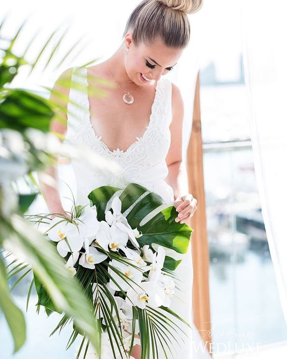 a glam tropical wedding bouquet with monstera leaves, greenery and white orchids for a bold look