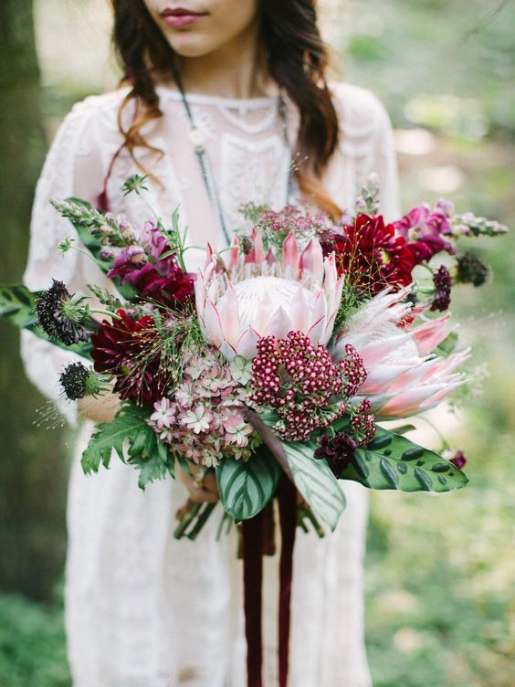 a lush and bold wedding bouquet with king proteas, burgundy and plum blooms and bold leaves for a fall boho bride