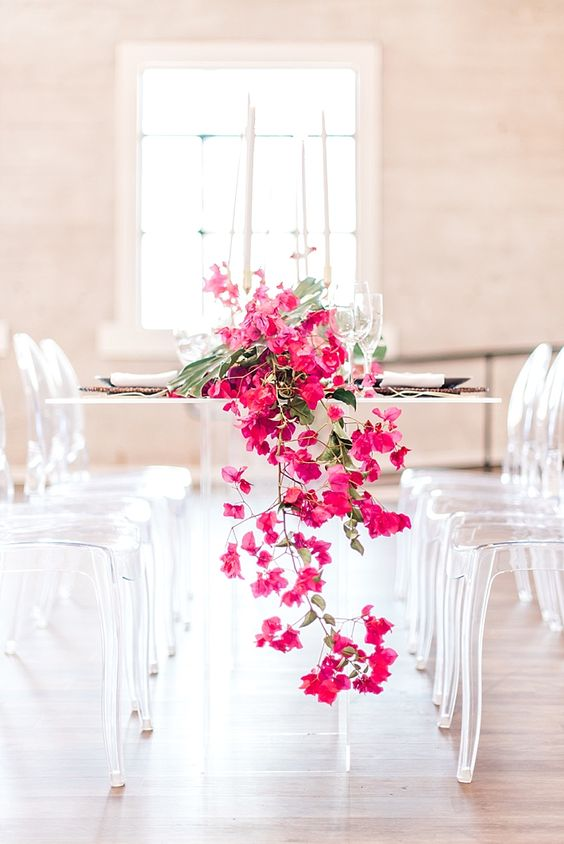 a modern tropical table runner with palm leaves and bold fuchsia blooms cascading down