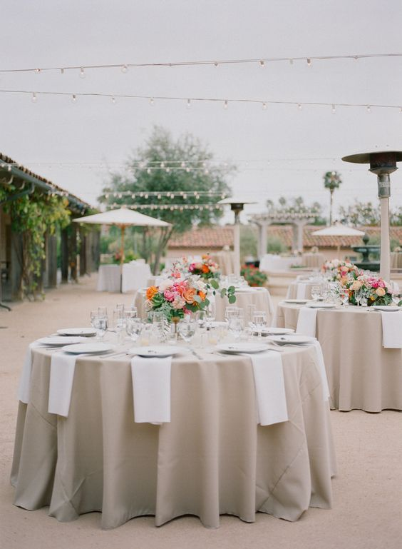 combine taupe tablecloths and creamy napkins for elegant table decor and spruce up the table setting with bright blooms