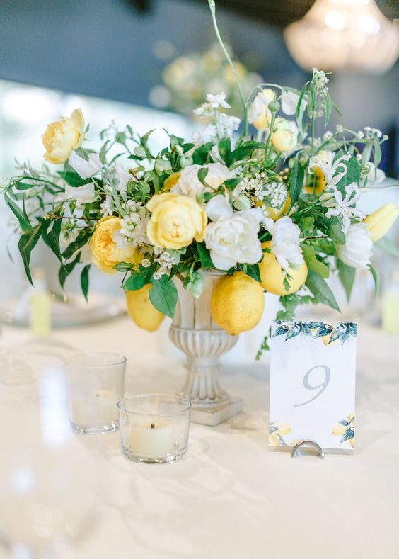 a chic summer centerpiece of an urn, white and yellow blooms and lemons hanging down