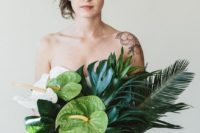 18 a chic textural and domensional bouquet with large tropical leaves, cascading greenery and orchids
