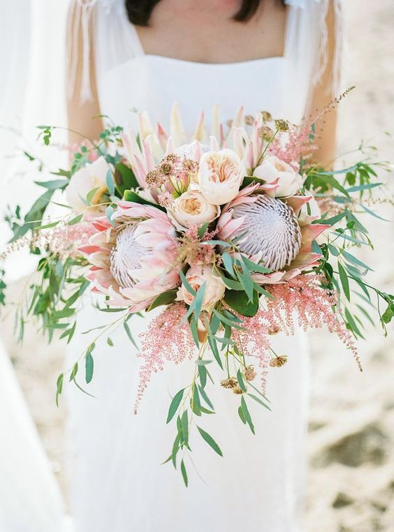 a lush bouquet with king proteas, blush peonies and lots of greenery and pink branches for a tender look